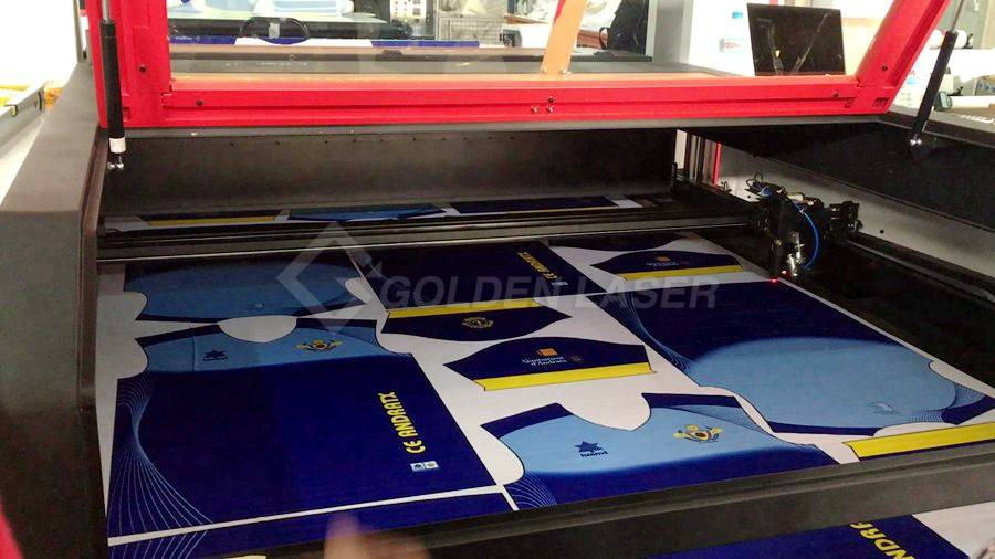 laser cutting sublimation prints of sportswear in European customer workshop
